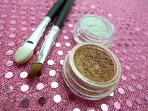 Mineral Cosmetics Display. Gold and white mineral cosmetics in clear pots with two applicator brushes on pretty feminine pink metallic display background Stock Images