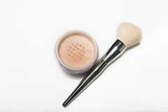 Mineral loose powder and cosmetic brush on a white background. Mineral loose powder and cosmetic brush isolated on a white background Stock Images