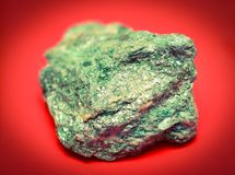 Mineral on red background, fuchsite Royalty Free Stock Image