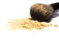 Mineral shimmer powder golden color with makeup brush. Close-up of crushed mineral shimmer powder golden color with makeup brush on white background. Shallow Stock Image