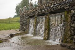 Mineral spring. Stream in the SPA. Curative water. Resort. Waterfalls. Summer. Clear and fresh water on the stone wall.  royalty free stock photography