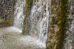 Mineral spring. Stream in the SPA. Curative water. Resort. Waterfalls. Summer. Clear and fresh water on the stone wall.  stock photography