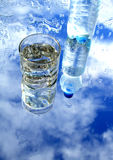 Mineral Water. Glass of mineral water with blebs on background with sky and bottle reverberation Stock Image