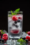 Mineral water with berries. A glass of chilled mineral water with ice cubes and berries near spilled blueberries, strawberries and raspberries on a black Stock Photos