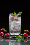 Mineral water with berries. A glass of chilled mineral water with ice cubes and berries near spilled blueberries, strawberries and raspberries on a black Royalty Free Stock Photo