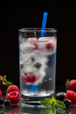 Mineral water with berries, ice cubes and blue straw. A glass of mineral water with ice cubes and berries, straw near spilled blueberries, strawberries Royalty Free Stock Photos