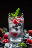 Mineral water with berries and ice cubes. A glass of chilled mineral water with ice cubes and berries near spilled blueberries, strawberries, raspberries and Stock Photo