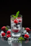 Mineral water with berries and ice cubes. A glass of chilled mineral water with ice cubes and berries near spilled blueberries, strawberries, raspberries and Stock Photos