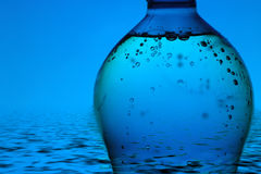 Mineral water bottle on blue background Royalty Free Stock Photos