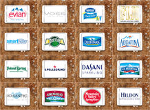 Mineral water brands and logos. Collection of top famous mineral water companies brands and vectors on white tablet on wooden background. brands like nestle Stock Photos