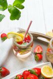 Mineral water with fresh strawberries, lemon and mint in jar royalty free stock photo