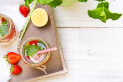 Mineral  water with fresh strawberries, lemon  and mint in jar Stock Images