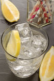 Mineral water with ice cubes and slice of lemon in a glass Stock Photo