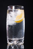 Mineral water with lemon. Mineral water with ice and lemon in a glass on a black background Royalty Free Stock Photos