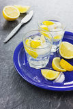 Mineral water with lemons and ice cubes. On a blue serving ceramic dish on a black stone surface Stock Photography
