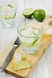 Mineral water with lime and ice cubes. With knife on a kitchen board on a white surface Royalty Free Stock Photography
