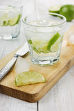 Mineral water with lime and ice cubes on a white surface. Mineral water with lime and ice cubes with knife on a kitchen board on a white surface Royalty Free Stock Photos