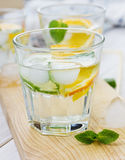 Mineral water with limes, oranges, lemons, ice and mint. On a wooden board Stock Photos