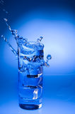 Mineral water splashing out from glass Stock Image