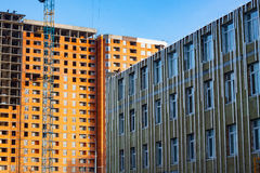 Mineral wool insulated facade and building with cranes Royalty Free Stock Photo