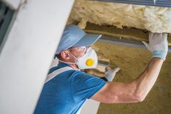 Mineral Wool Insulation. By Professional Insulating Worker. Caucasian Construction Worker in His 30s Royalty Free Stock Photography