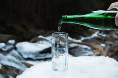Mineralisk mineralvatten hälls från en glass grön flaska in i en klar glass dryckeskärl Fotografering för Bildbyråer