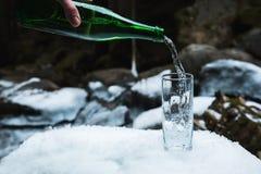 Mineralisk mineralvatten hälls från en glass grön flaska in i en klar glass dryckeskärl Arkivbild