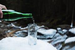 Mineralisk mineralvatten hälls från en glass grön flaska in i en klar glass dryckeskärl Arkivfoto