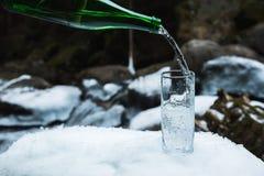 Mineralisk mineralvatten hälls från en glass grön flaska in i en klar glass dryckeskärl Royaltyfri Fotografi