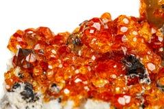 Mineralisk sten Spessartine, apelsin, röd granatrött för makro med kvarts arkivbild
