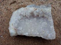 Mineralisk yttersida för Crystal stenmakro på sanden, bakgrundstapet royaltyfri bild