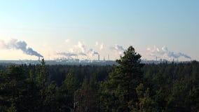 Mineraliskt oljeraffinaderi med att röka lampglas på horisonten och den naturliga barrskogen i förgrunden stock video
