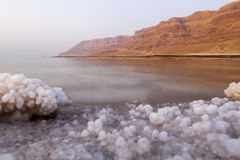 Minerals. Dead sea lanscape with minehral structures on the shore and desert mountains in the background Royalty Free Stock Photos