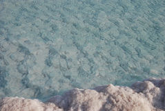 Minerals of Dead Sea. Coastline of Dead Sea : salt on coast and in water Royalty Free Stock Image