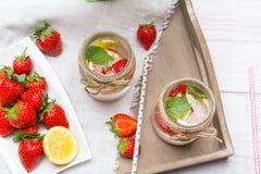 Mineralvatten med den nya jordgubbar, citronen och mintkaramellen i krus Arkivbilder