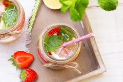 Mineralvatten med den nya jordgubbar, citronen och mintkaramellen i krus Arkivfoto