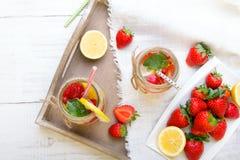 Mineralvatten med den nya jordgubbar, citronen och mintkaramellen i krus Royaltyfria Bilder