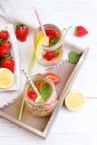 Mineralvatten med den nya jordgubbar, citronen och mintkaramellen i krus Arkivbild