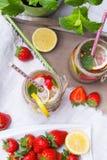 Mineralvatten med den nya jordgubbar, citronen och mintkaramellen i krus Arkivfoton