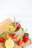 Mineralvatten med den nya jordgubbar, citronen och mintkaramellen i krus Royaltyfri Bild