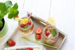 Mineralvatten med den nya jordgubbar, citronen och mintkaramellen i krus Fotografering för Bildbyråer