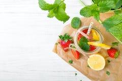 Mineralvatten med den nya jordgubbar, citronen och mintkaramellen i krus Royaltyfri Foto