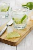 Mineralvatten med limefrukt- och iskuber på en vit yttersida Royaltyfria Foton