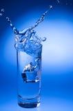 Mineralwasser, das heraus vom Glas spritzt Stockbild