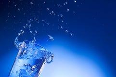 Mineralwasser, das heraus vom Glas spritzt Stockbilder