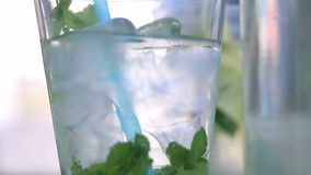 Mineralwasser im Glas mit Eiswürfel-, Minzen-, Kalk- und Zitronenscheiben auf Straßenlebensmittelfestival stock video footage