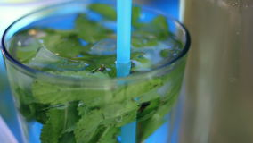 Mineralwasser im Glas mit Eiswürfel-, Minzen-, Kalk- und Zitronenscheiben auf Straßenlebensmittelfestival stock footage