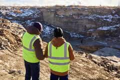 Miners on Excavation Site. Back view portrait of two industrial workers wearing reflective jackets, one of them African, standing on cliff overlooking mineral Stock Photo