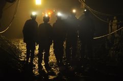 Miners. A group of five miners on duty underground, in silhouette with their headlamps on Royalty Free Stock Photos