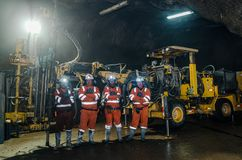 Miners and large machines inside the mine stock photo